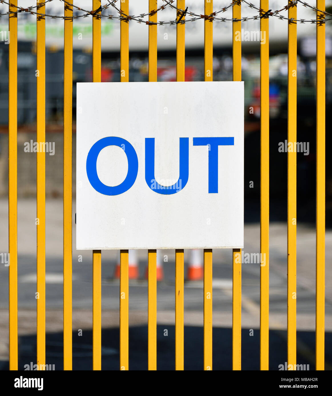 'OUT' sign and razor wire on metal gate to industrial site. Parkside Road, Kendal, Cumbria, England, United Kingdom, Europe. - Stock Image