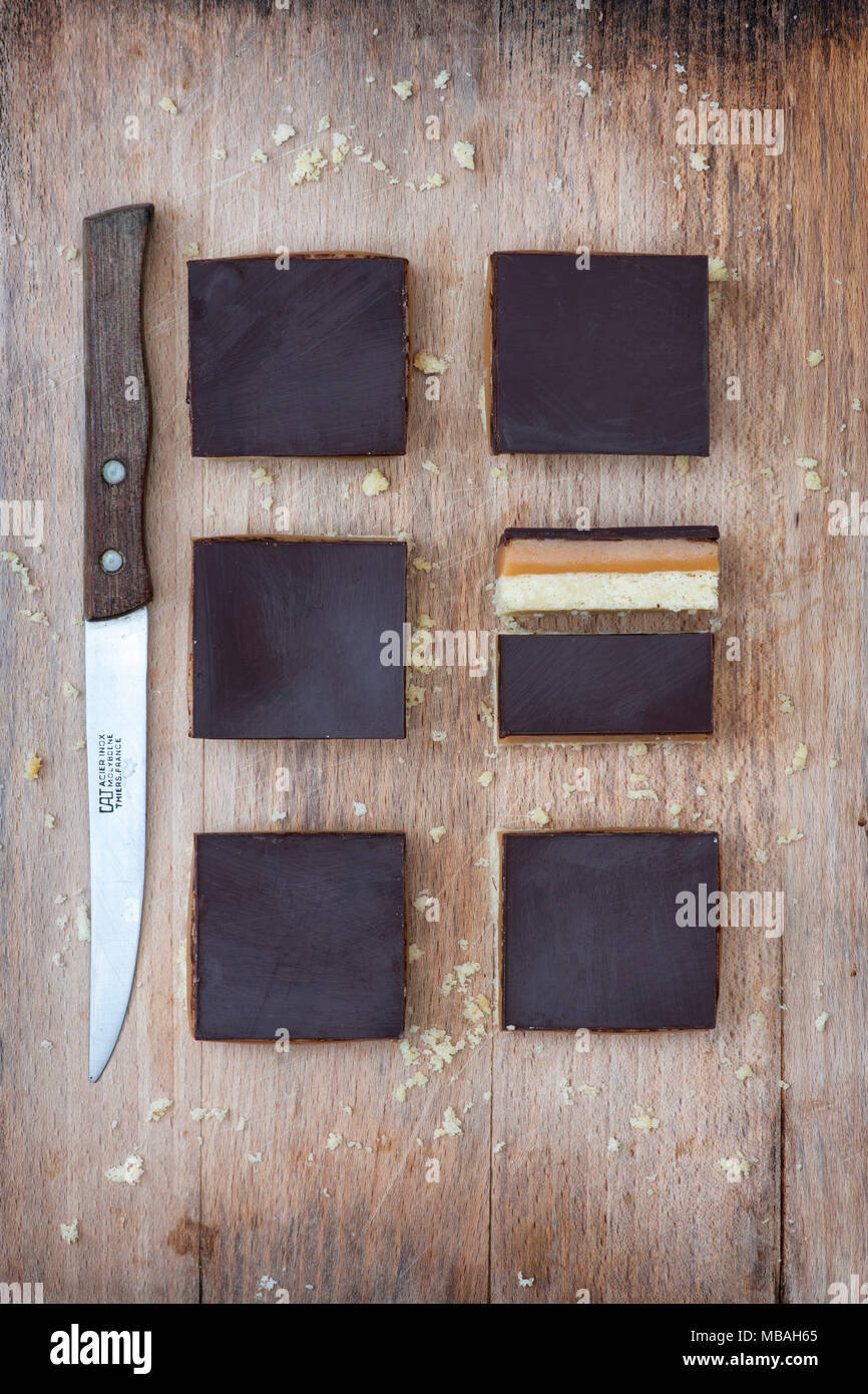 Caramel shortbread / Millionaires shortbread squares with a vintage kitchen knife on a wooden chopping board Stock Photo