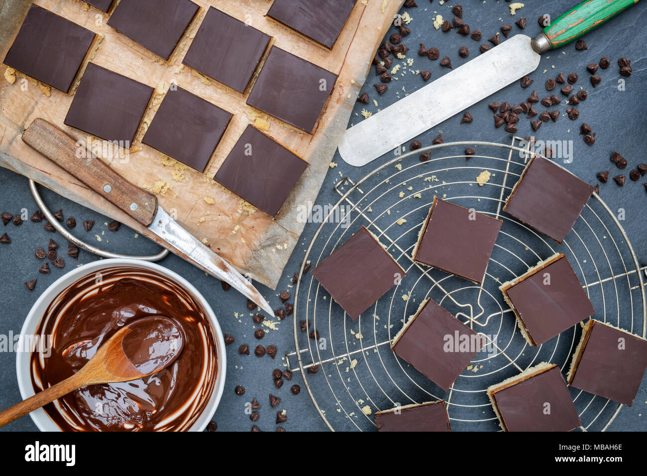 Caramel shortbread / Millionaires shortbread squares with a pallet knife and melted dark chocolate in a bowl on a slate background - Stock Image