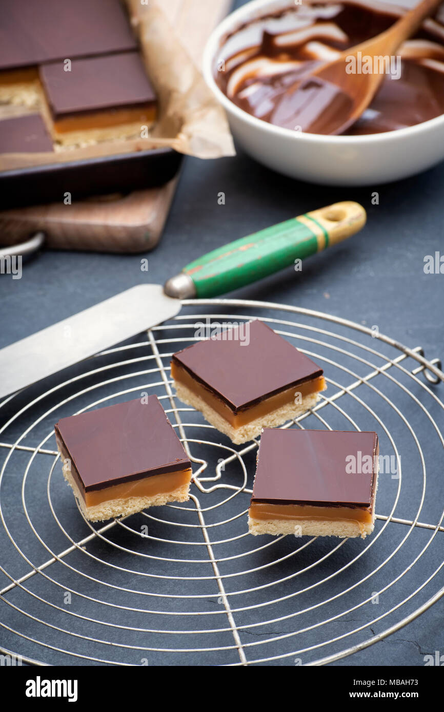 Caramel shortbread / Millionaires shortbread squares with a pallet knife on a round vintage wire cooling rack on a slate background - Stock Image