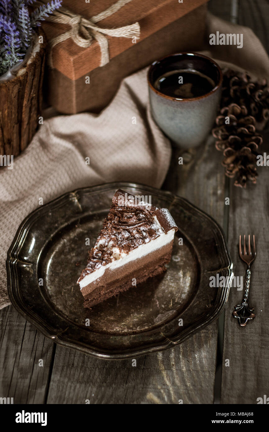 Chocolate birthday cake on a rustic vintage plate and wooden table - Stock Image