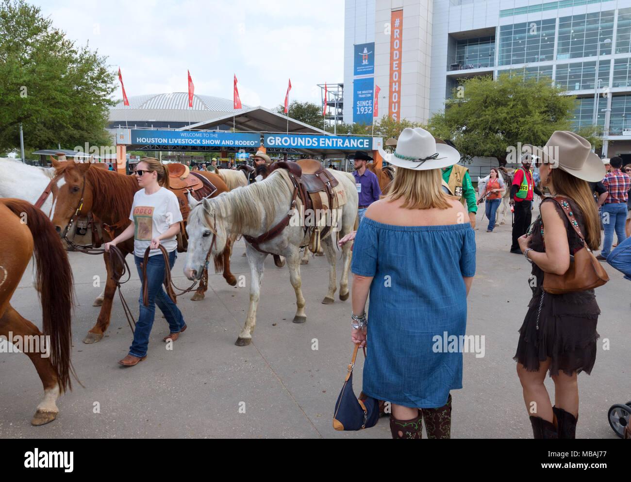 Two Texas women watching horses, Houston Livestock Show and Rodeo, Houston, Texas USA - Stock Image