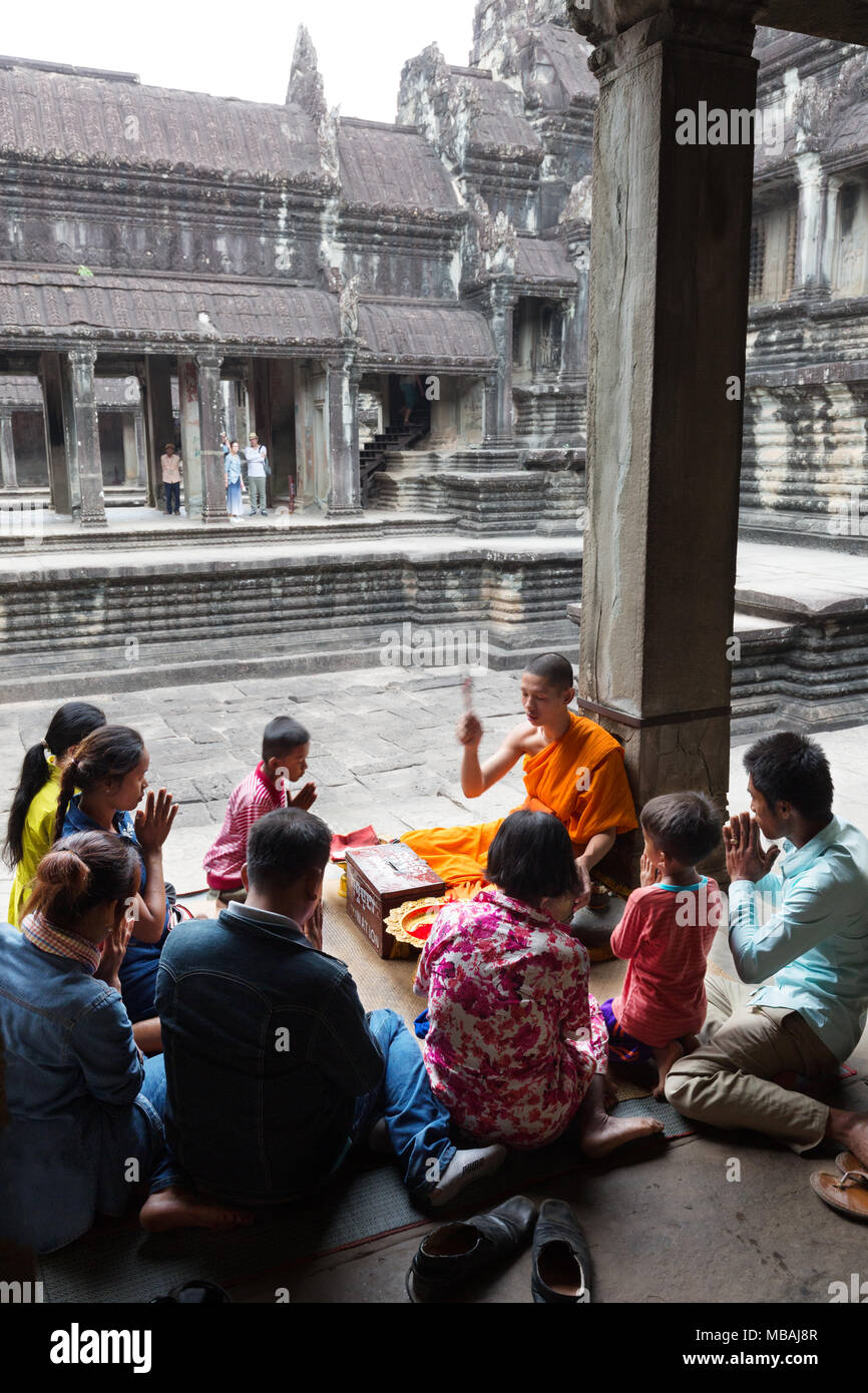 A Buddhist monk giving a blessing to a cambodian local family, Angkor Wat temple, Angkor site, Siem Reap, UNESCO World Heritage site, Cambodia, Asia - Stock Image
