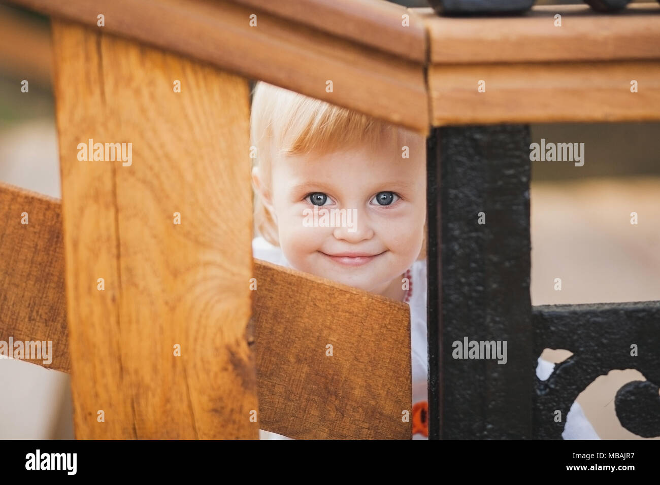 1 year old little caucasian girl palaing hide and seek game outdoors on sunny warm summer day. Closeup portrait of tricky face of blonde baby hiding f - Stock Image