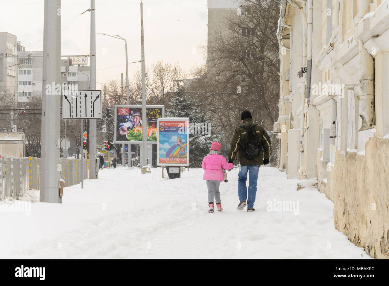 VARNA, BULGARIA, FEBRUARY 28, 2018: father and daughter walking under a snow storm in Varna - Stock Image
