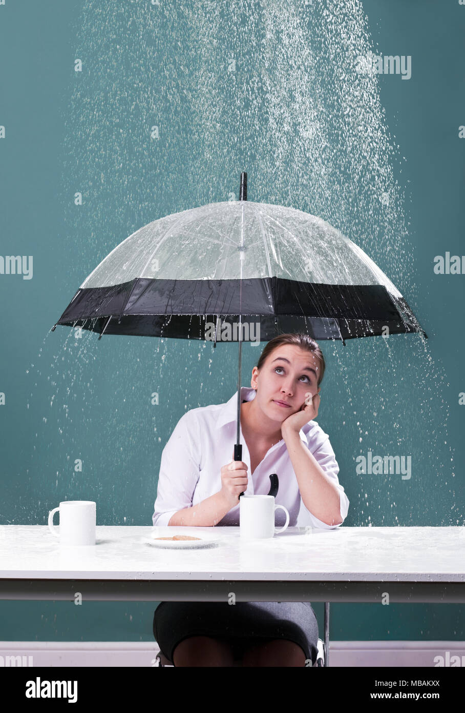 Woman sitting at a table with umbrella in the rain - Stock Image