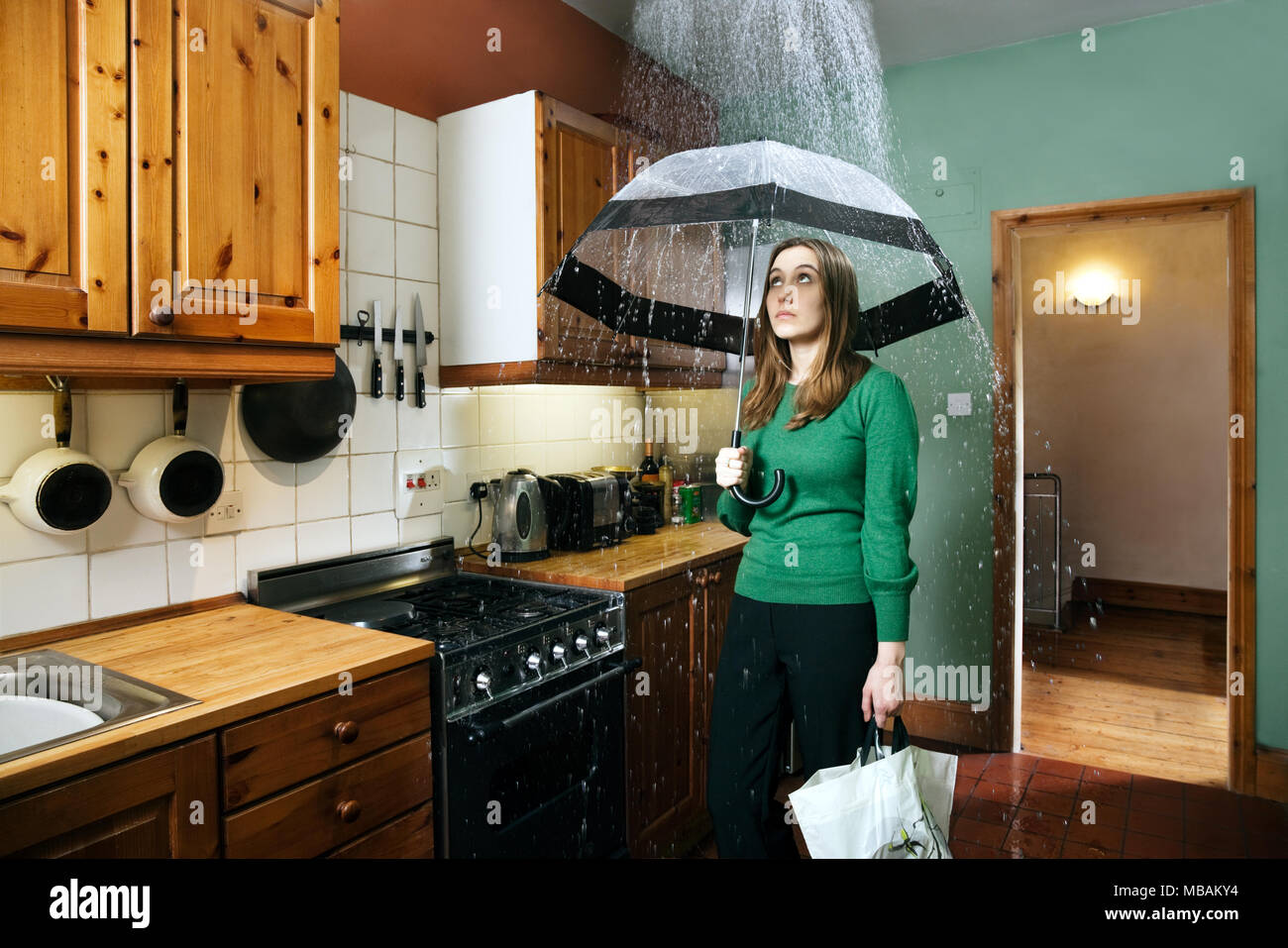 Woman standing in kitchen with umbrella under shower of rain, indoors - Stock Image