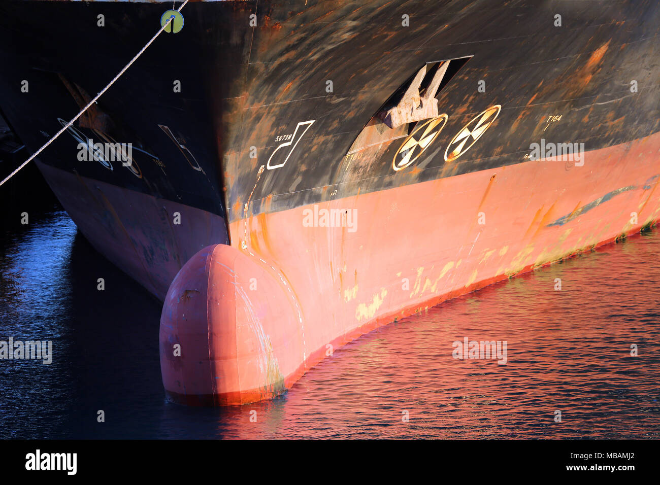 bulbous bow detail of cargo ship showing mooring line, water line, anchor, and red water reflections - Stock Image