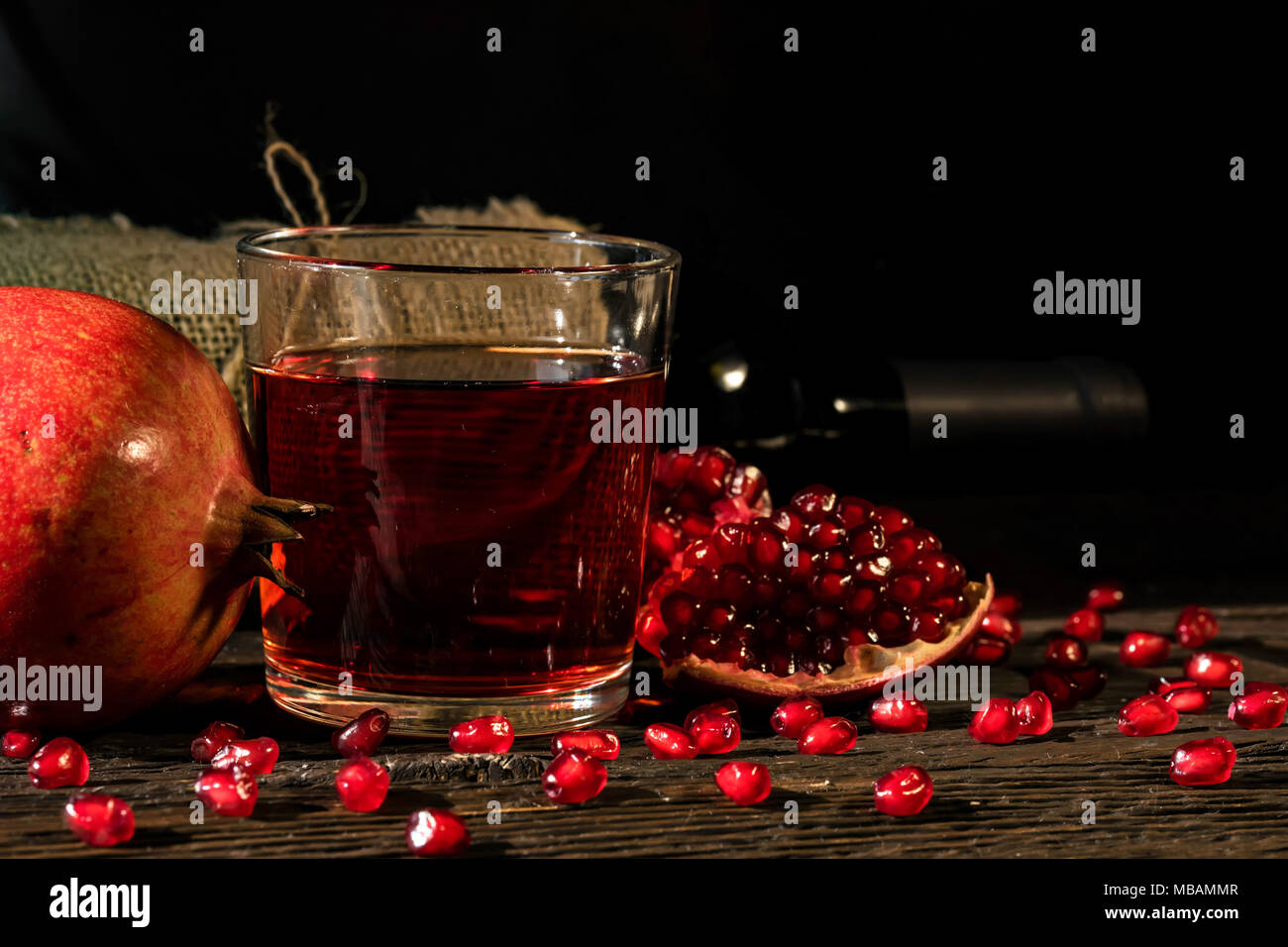 Pomegranate fruit, wine in glass and wine bottle - Stock Image