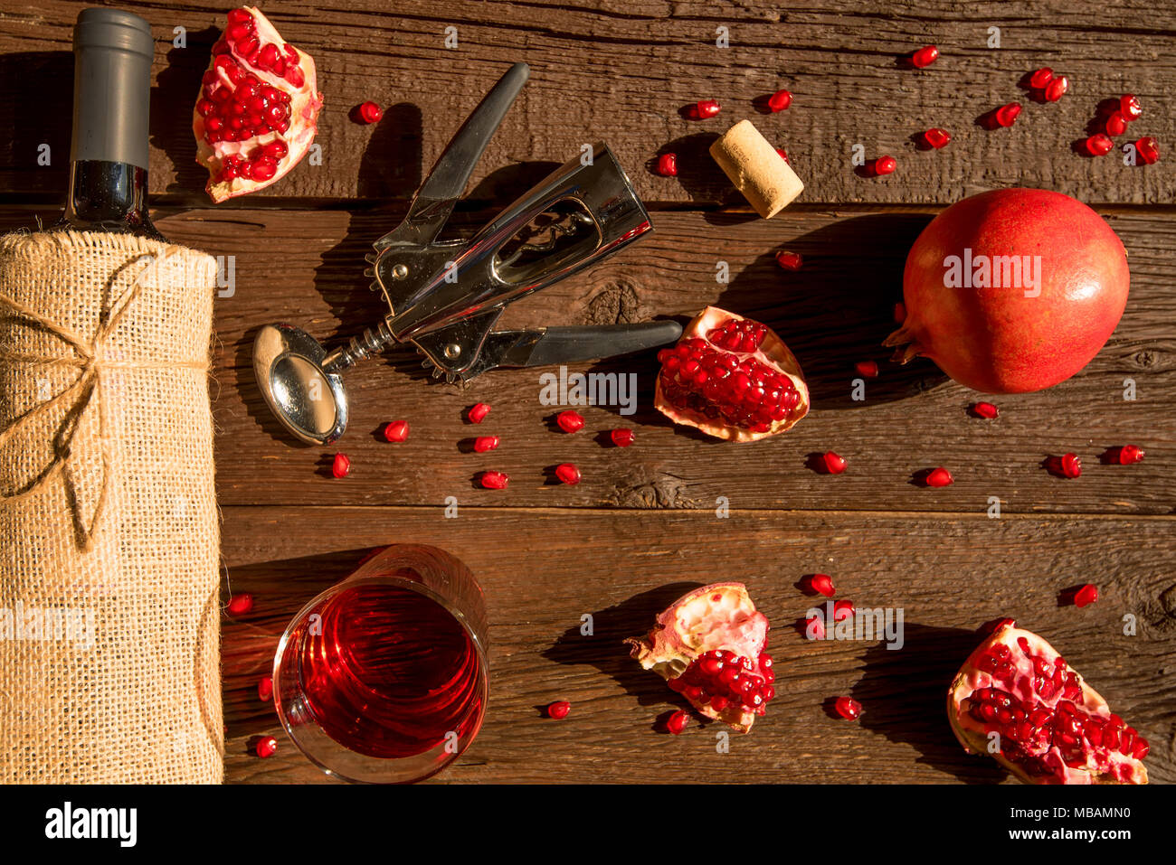 Top view pomegranate wine, bottle opener and fruit - Stock Image