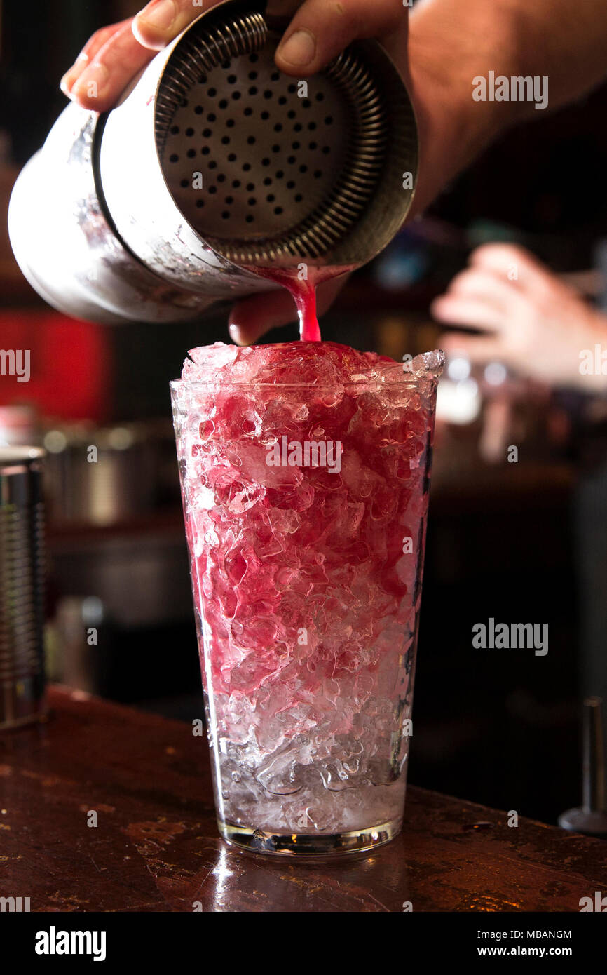 closeup of a barman making a red cocktail, pouring it into its glass full of crushed ice. - Stock Image