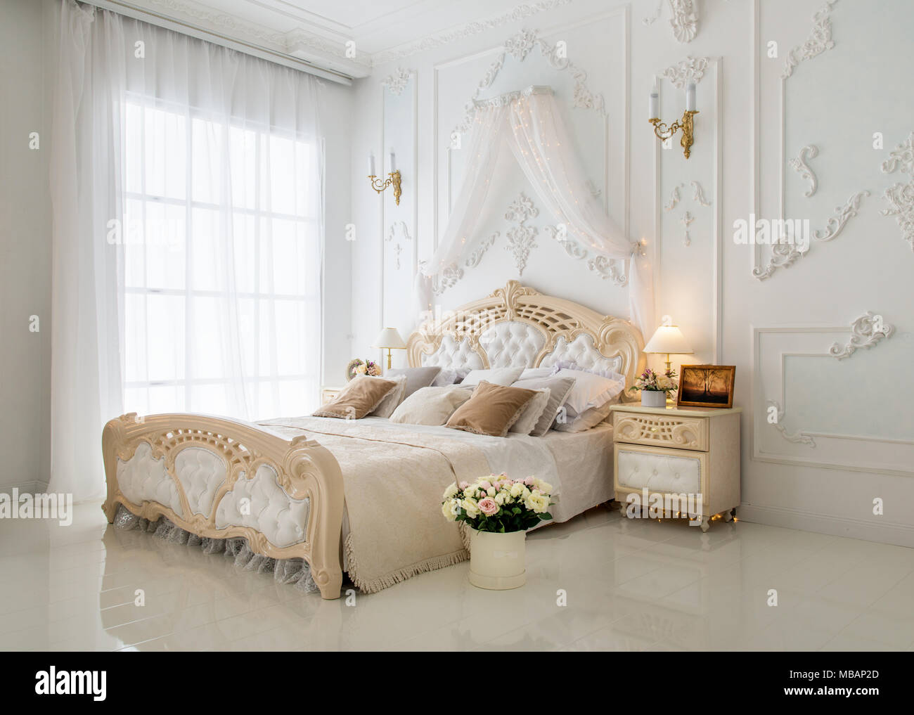 Elegant white classic bedroom with beautiful bouquet - Stock Image