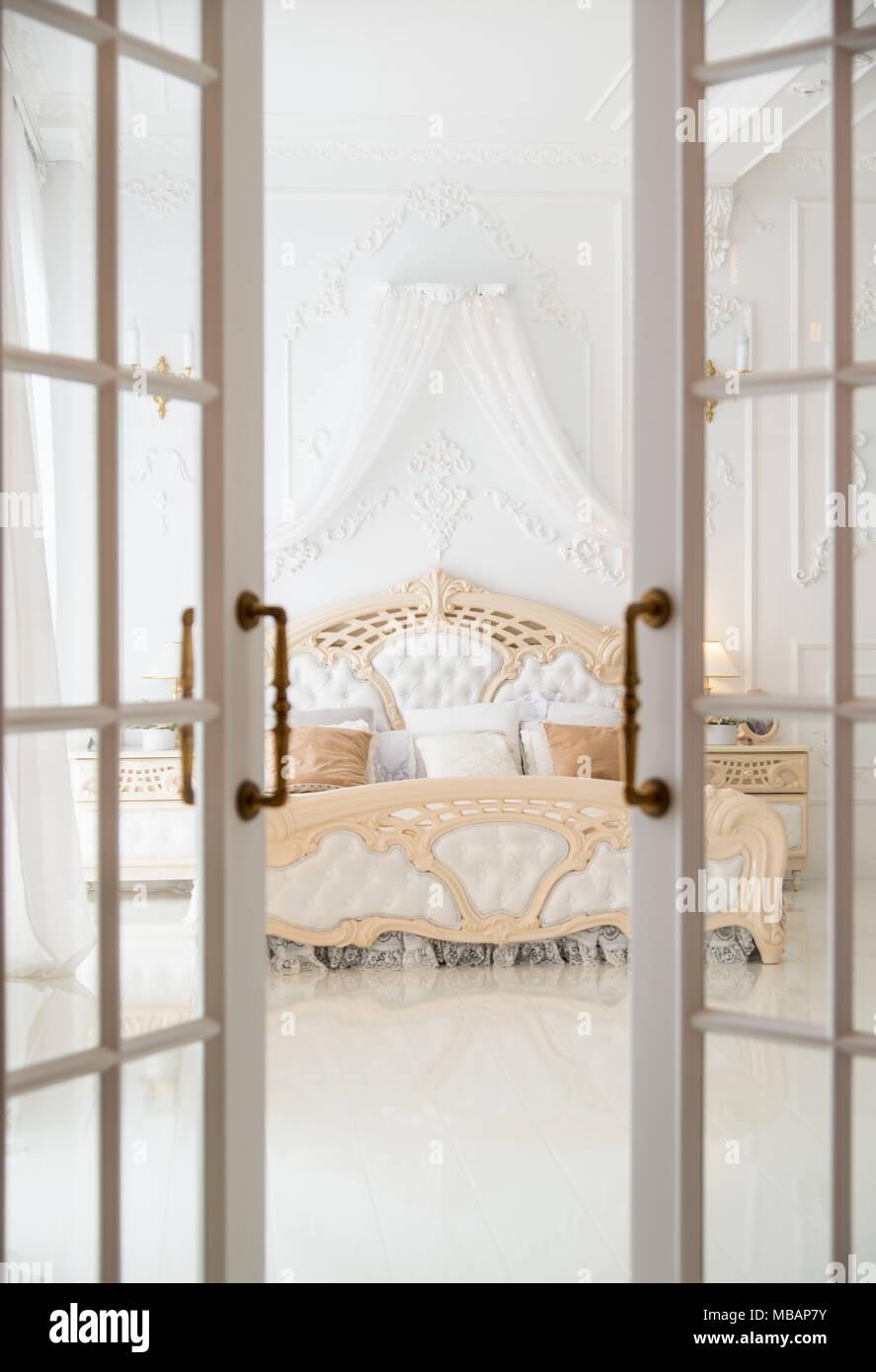 Open door leading to white classic bedroom - Stock Image