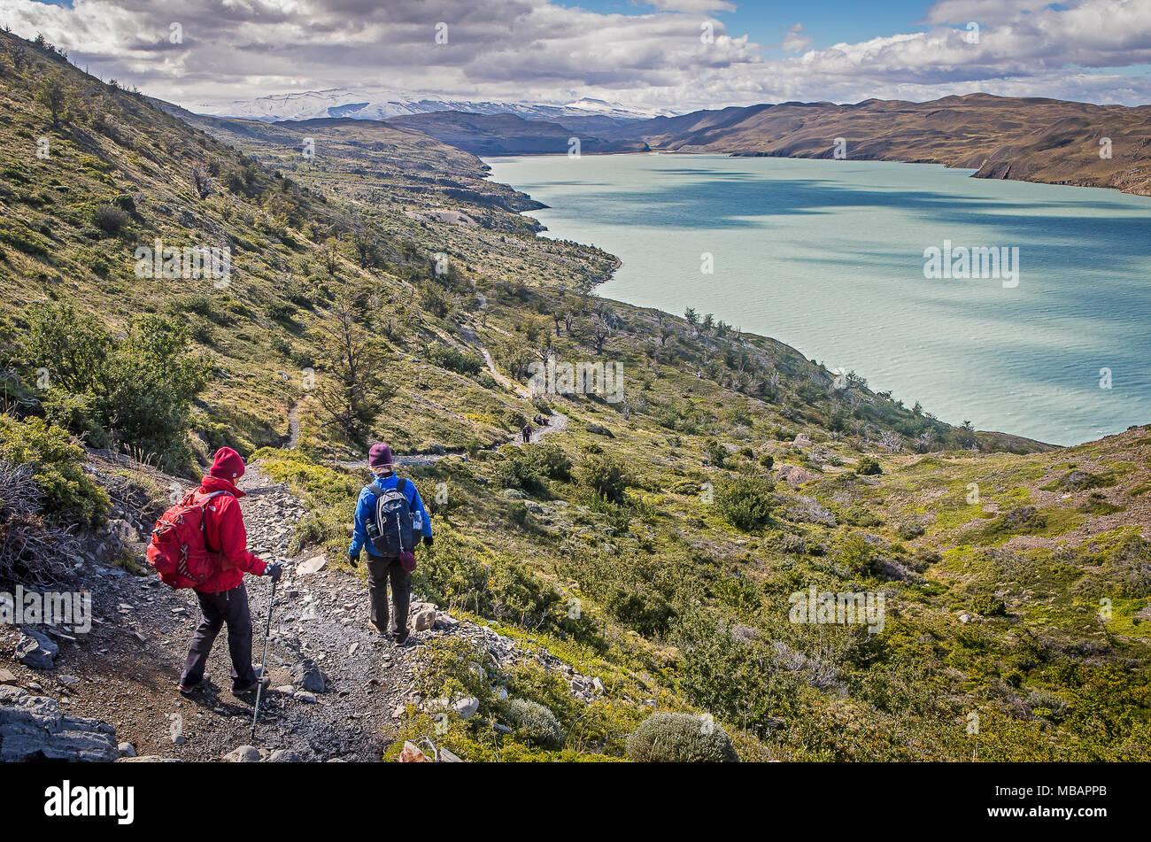Hikers walking, in background Lago Nordenskjöld, Torres del Paine national park, Patagonia, Chile - Stock Image