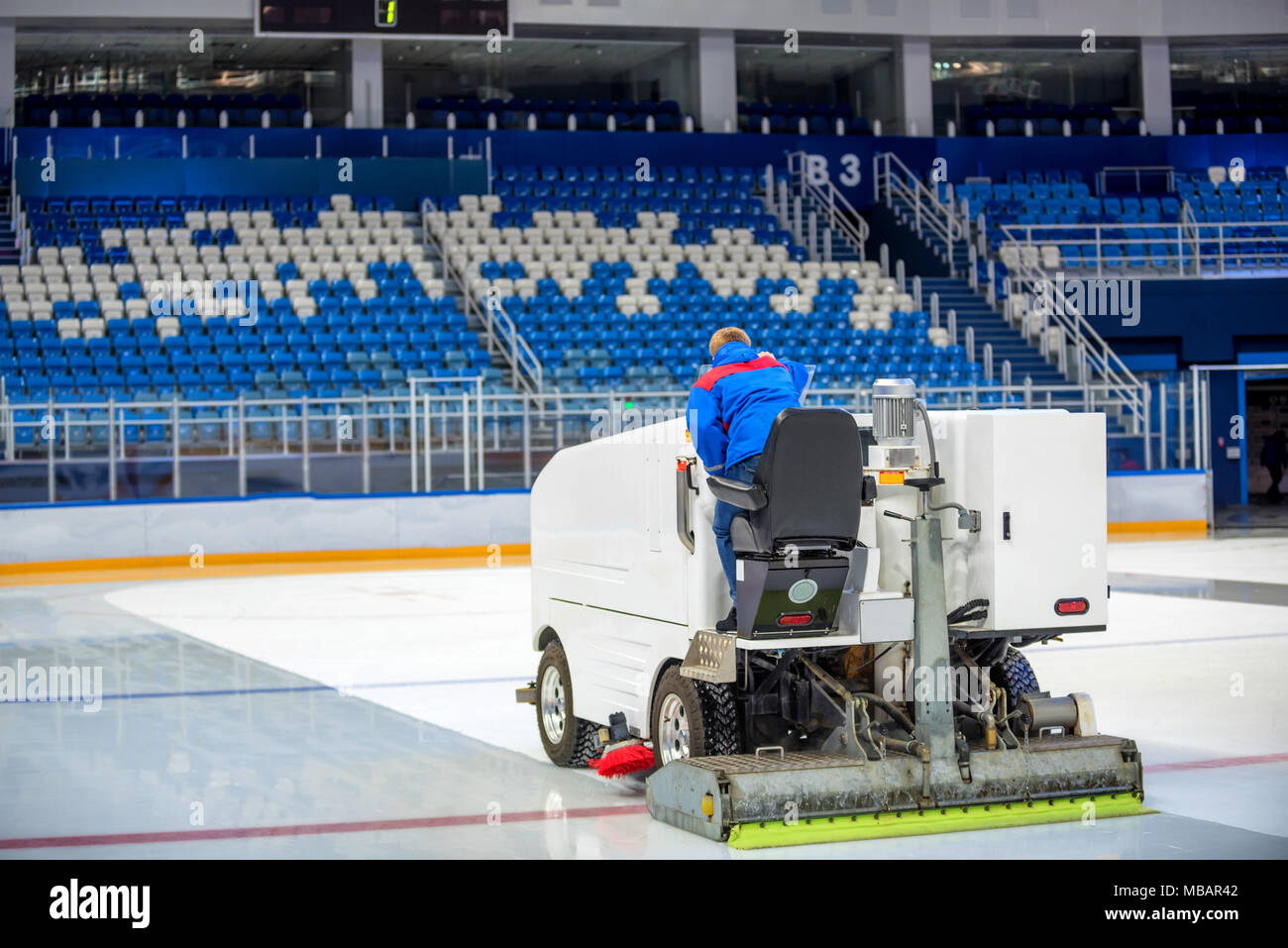 Resurfacing machine cleans ice of hockey rink - Stock Image