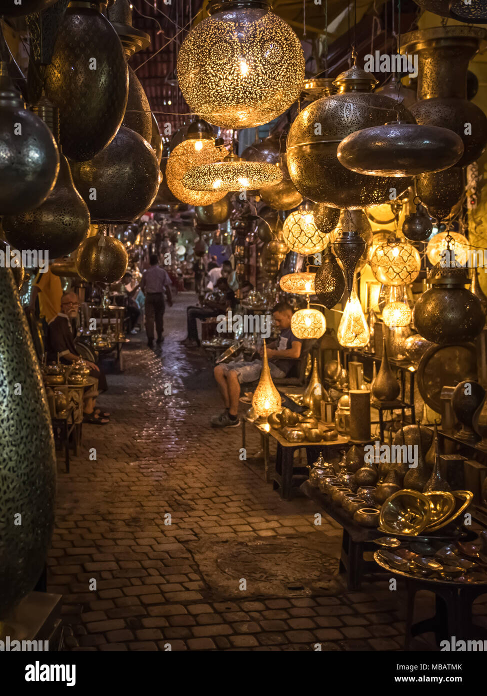 Glowing lamps fill a souk passageway in Marrakech, Morocco. The photo was taken at night when many of the lamps were lit. - Stock Image