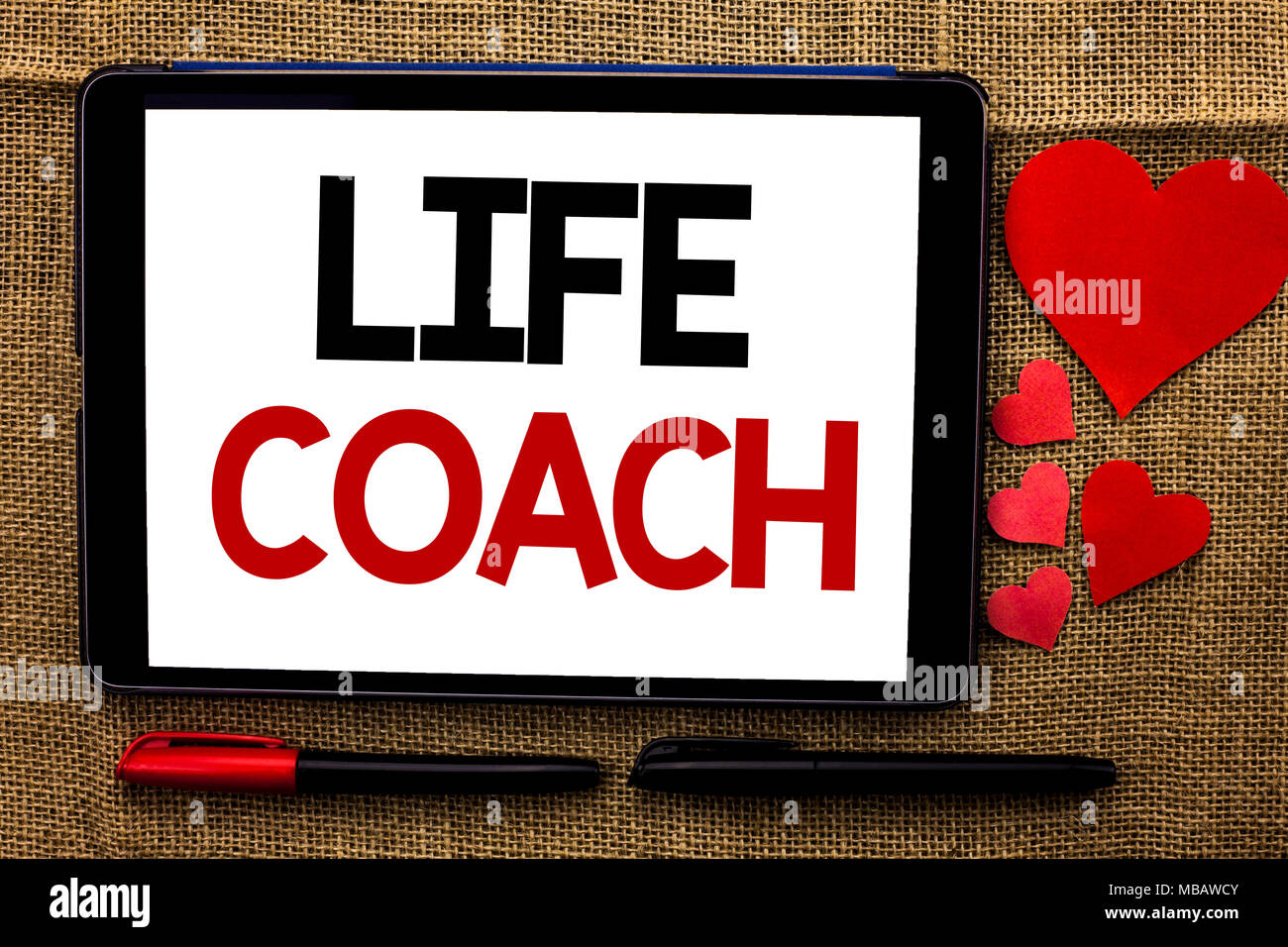 Handwriting text writing Life Coach. Concept meaning Mentoring Guiding Career Guidance Encourage Trainer Mentor written Tablet the jute background Hea - Stock Image