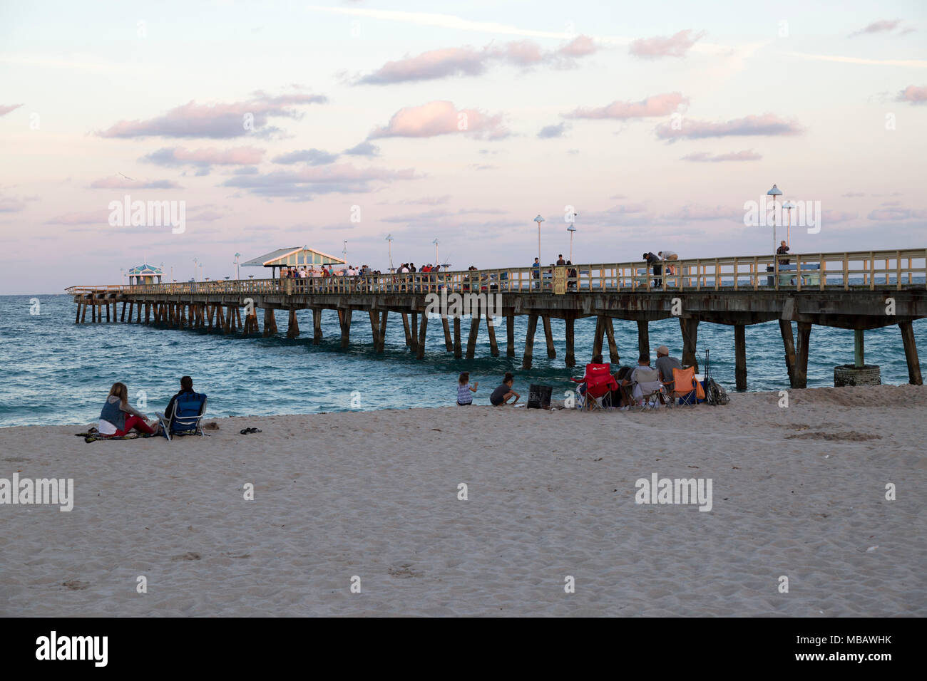 People gathered on pier at sunset in pompano beach, Florida - Stock Image