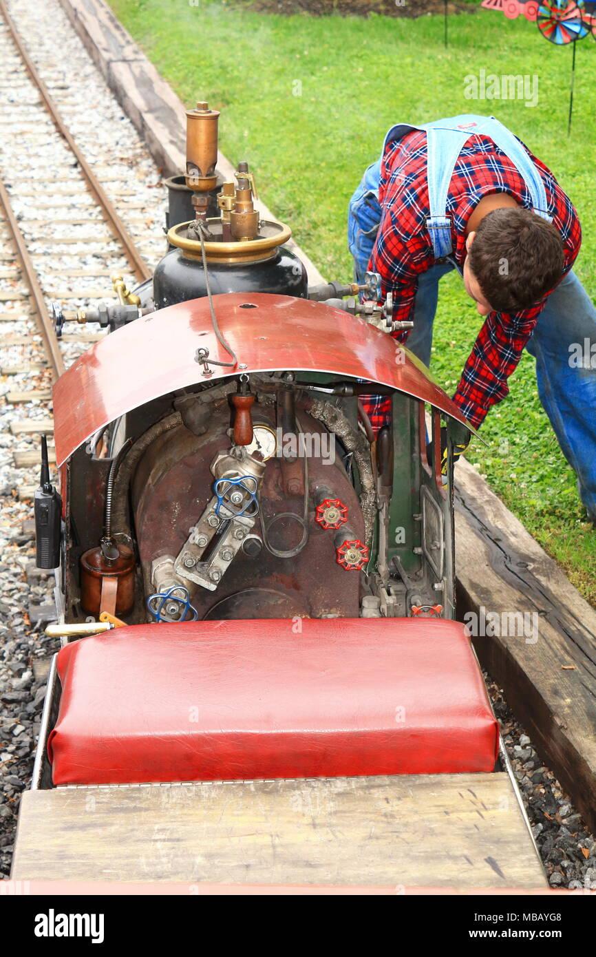 Engineer preparing a miniature steam locomotive for a run - Stock Image