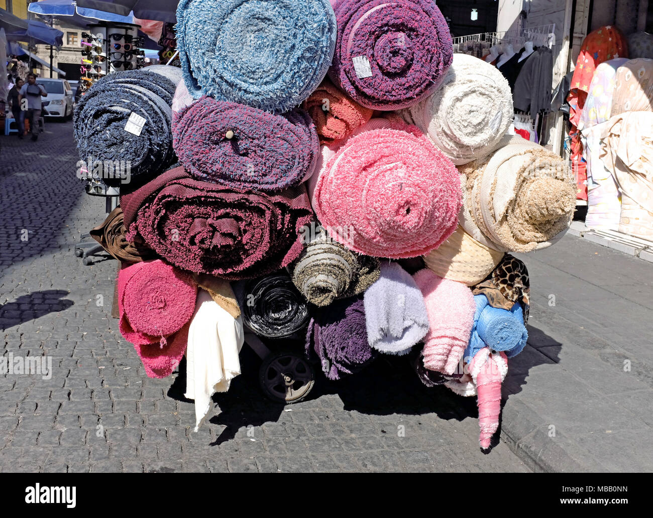 Rolls of carpeting are transported through the marketplace in the historic center of Mexico City, Mexico. - Stock Image