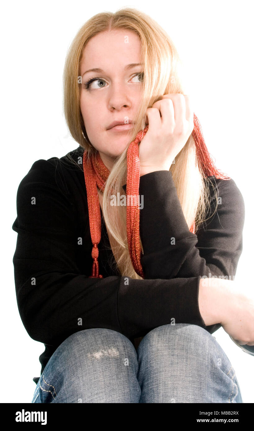 pretty blonde in black coat, blue jeans and red scarf on white - Stock Image