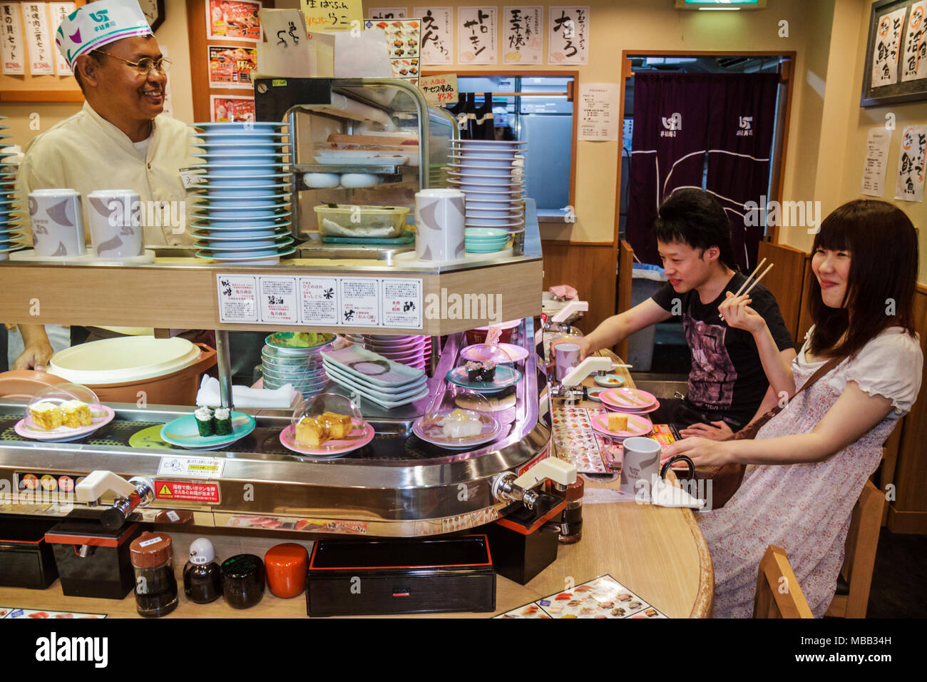 Tokyo Japan Ikebukuro kanji hiragana katakana characters sushi bar restaurant conveyor belt Asian man woman couple customers che - Stock Image