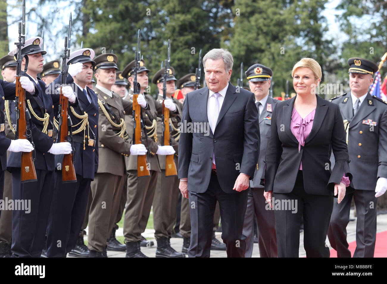 (180410) -- ZAGREB, April 10, 2018 (Xinhua) -- Visiting Finnish President Sauli Niinisto (L Front) and Croatian President Kolinda Grabar-Kitarovic (R Front) inspect the guard of honor during a welcoming ceremony in front of the Presidential Palace in Zagreb, capital of Croatia, on April 10, 2018. Sauli Niinisto is on a state visit to Croatia from Tuesday to Thursday. (Xinhua/Patrik Macek) (zjl) - Stock Image