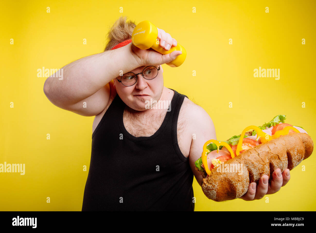 Fatigued fat man sweats while lifting burger - Stock Image