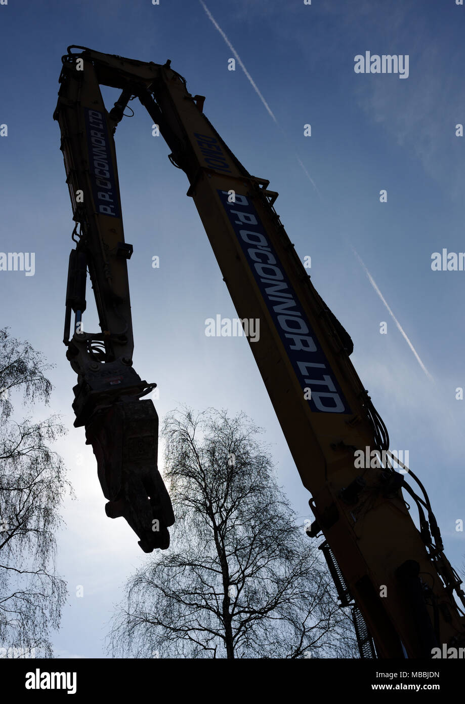 High reach hydraulic demolition excavator boom and concrete crusher attachment backlit by sun in bury lancashire - Stock Image