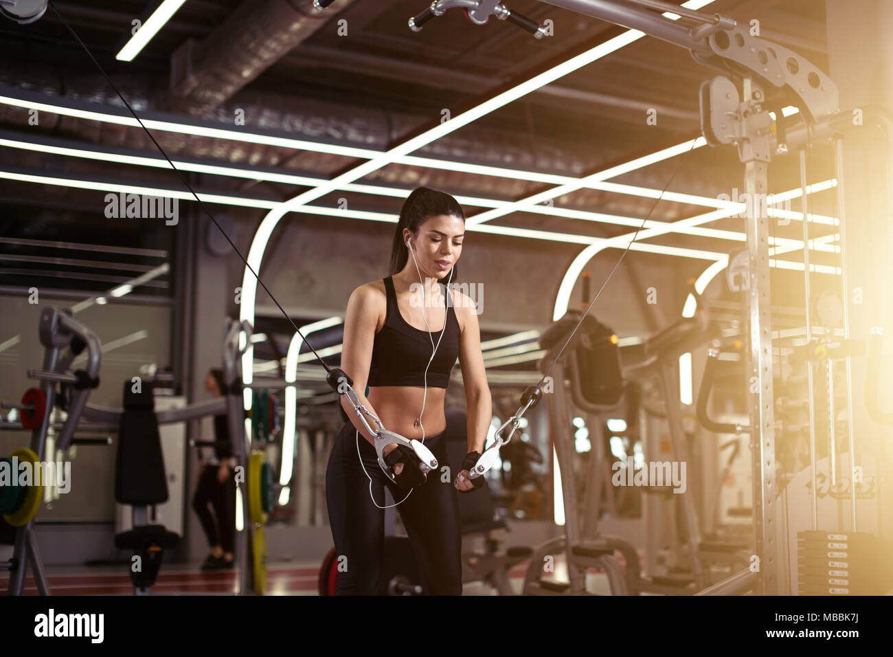 fit woman execute exercise with exercise-machine Cable Crossover in gym - Stock Image