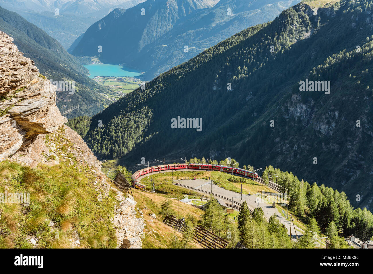 Mountain train at Alp Gruem train station, with the Valposchiavo in the background, Engadin, Switzerland | Bergzug an der Alp Gruem Zugstation mit dem - Stock Image