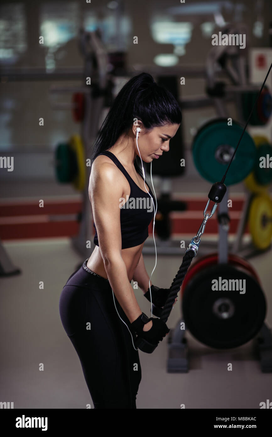 woman doing exercise at crossover machine in gym - Stock Image