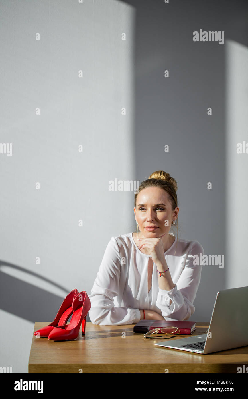 smiling businesswoman dreaming of future success at workplace - Stock Image