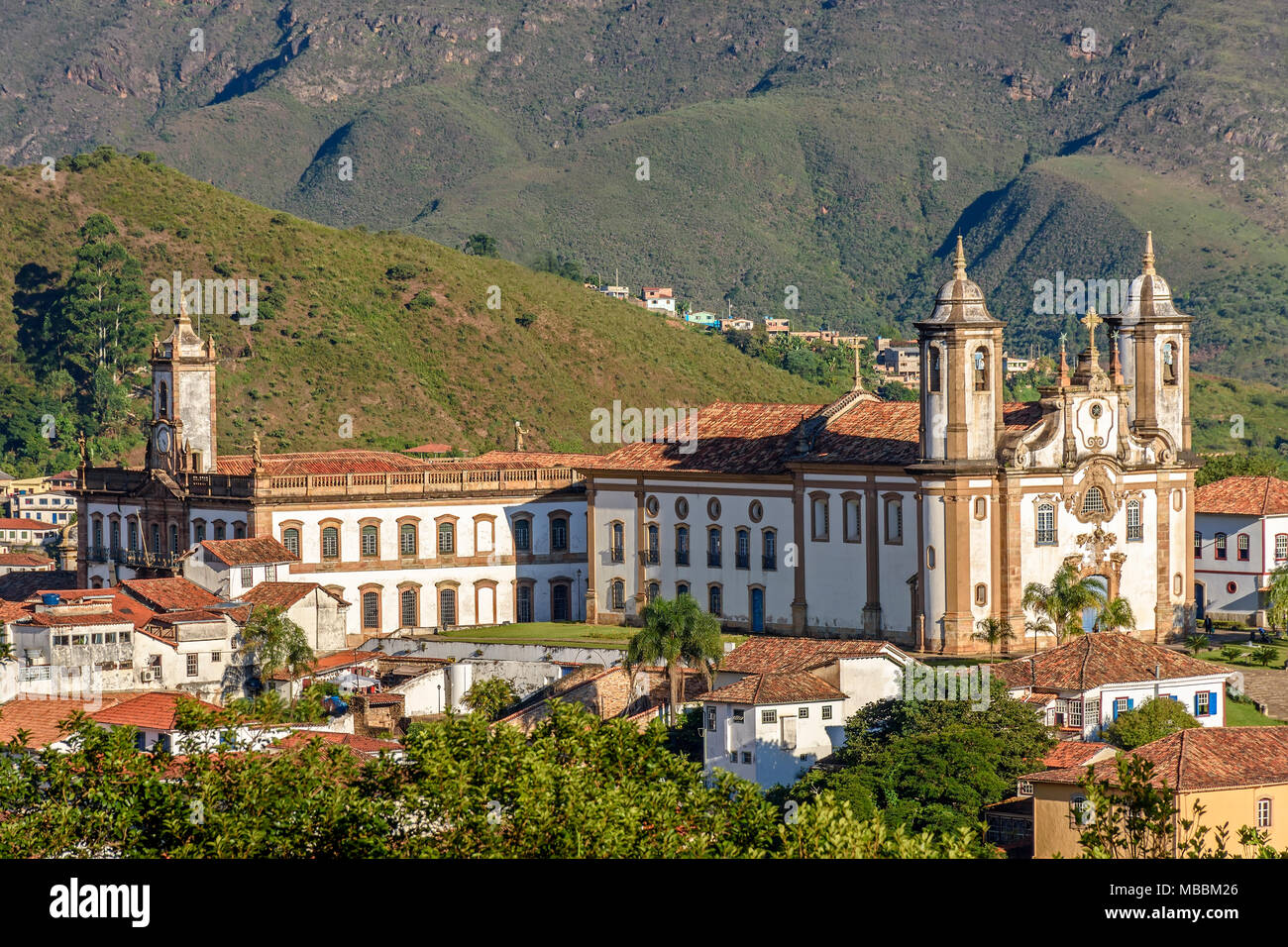 Top view of the center of the historic Ouro Preto city in Minas Gerais, Brazil with its famous churches and old buildings with hills in background - Stock Image