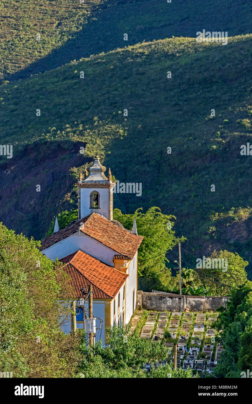 View from the top and behind old church in the city of Ouro Preto in Minas Gerais with a small graveyard beside and the hills in the background - Stock Image