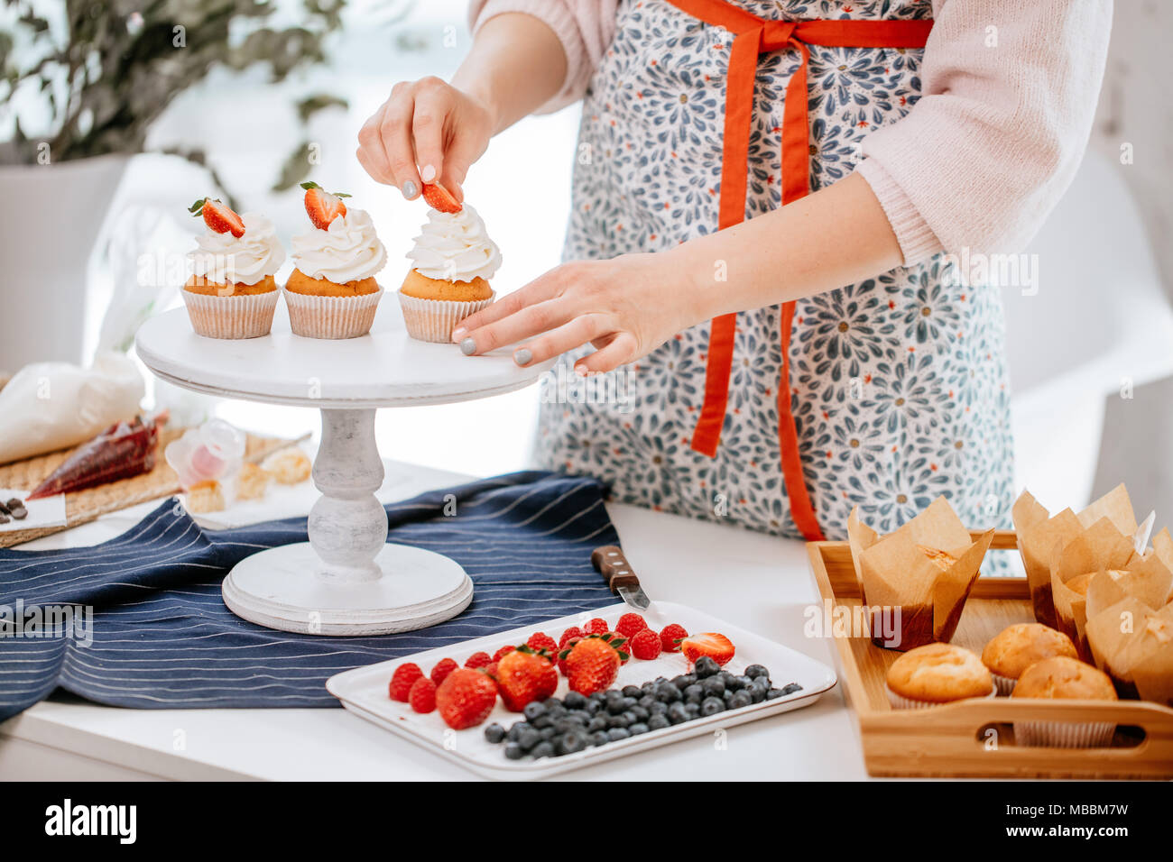 process of decorating cupcakes with berries - Stock Image
