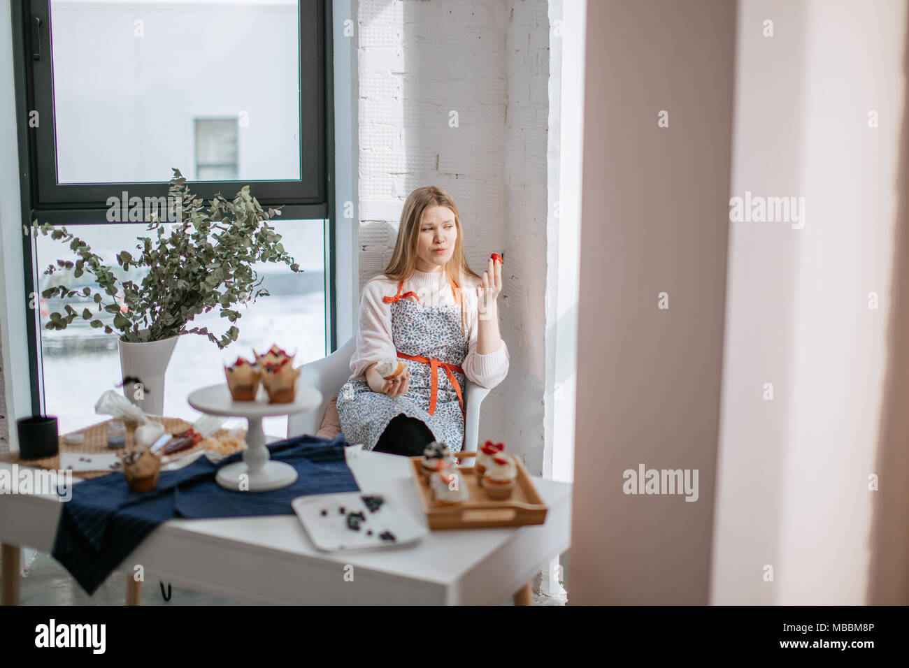 Beautiful young woman eating cupcake while sitting near window at cafe - Stock Image