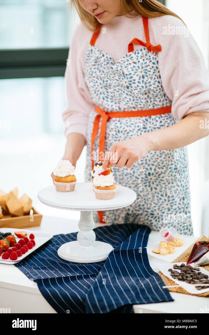 Bakery Chef in process of decorating cupcakes. - Stock Image