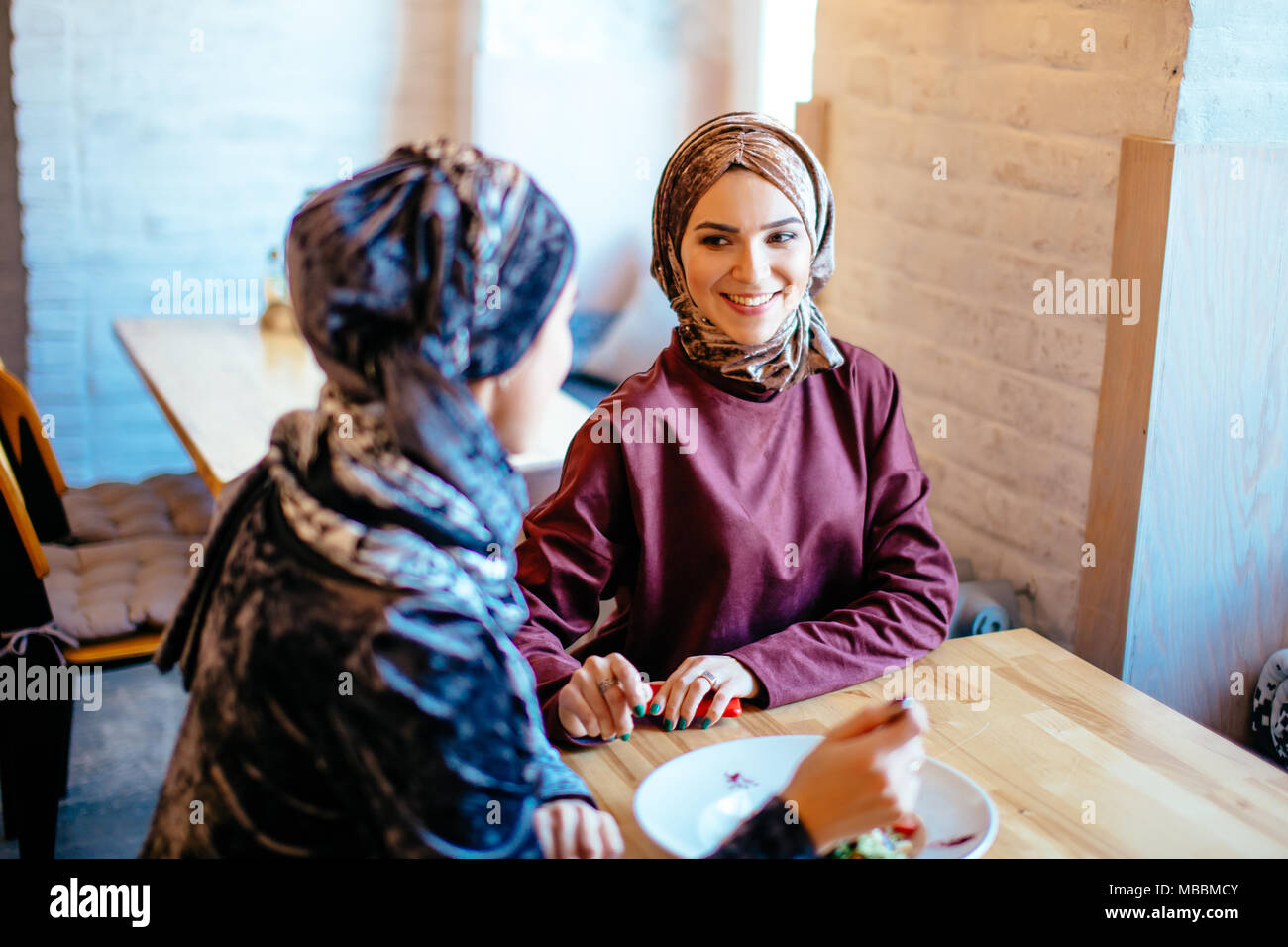 Two Muslim women in cafe, friends meeting - Stock Image