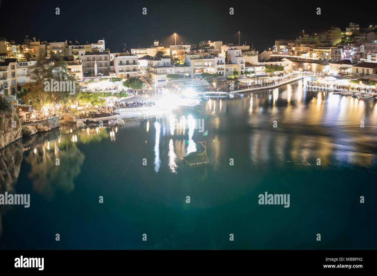 Agios Nikolaos, Crete, Greece. Cityscape with the night view to the internal lake or bay. Water reflections in the bay. Lights of the town reflected. - Stock Image
