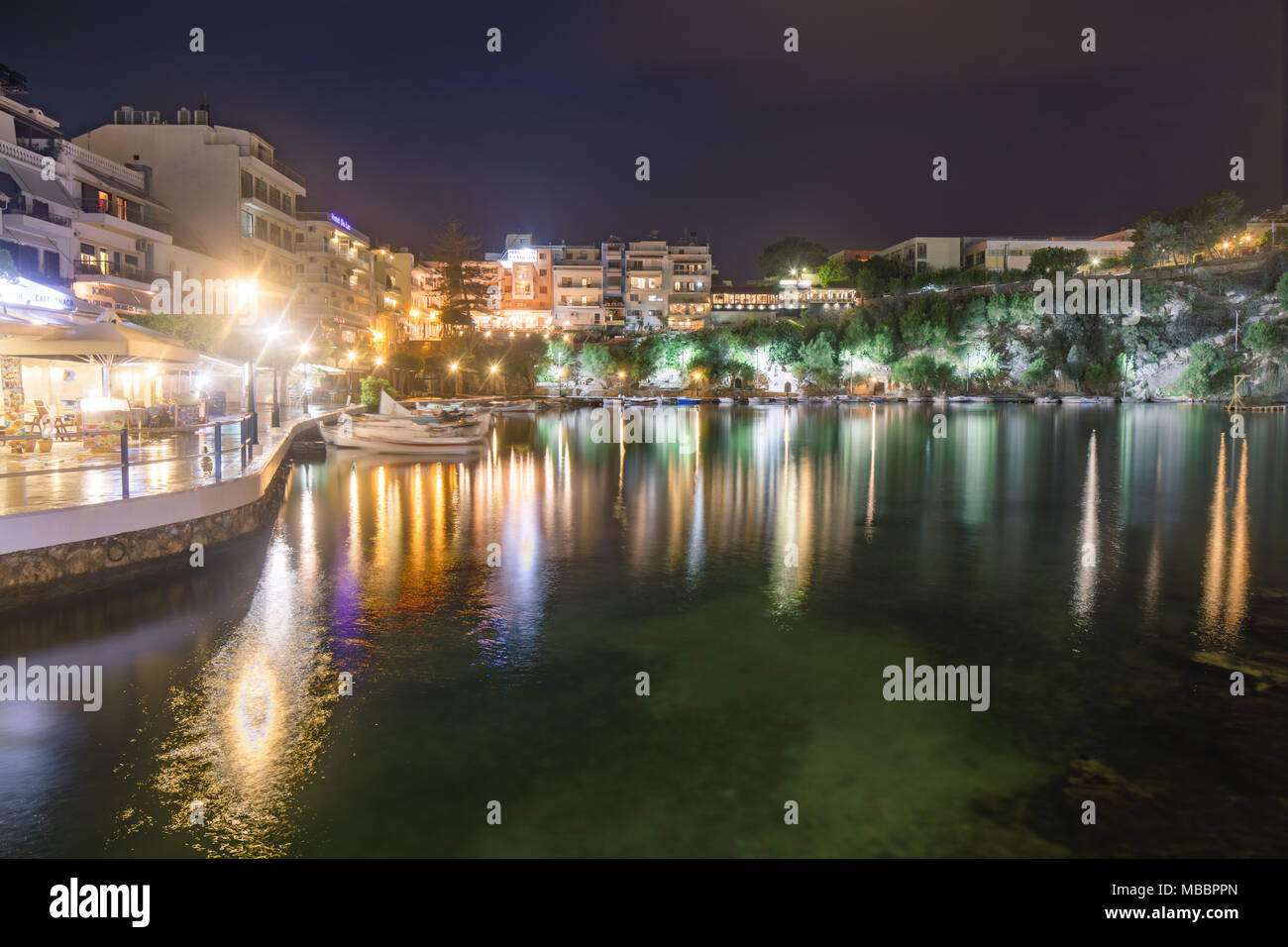 Cityscape with the night view to the lake and water reflections. Agios Nikolaos, Crete, Greece. - Stock Image