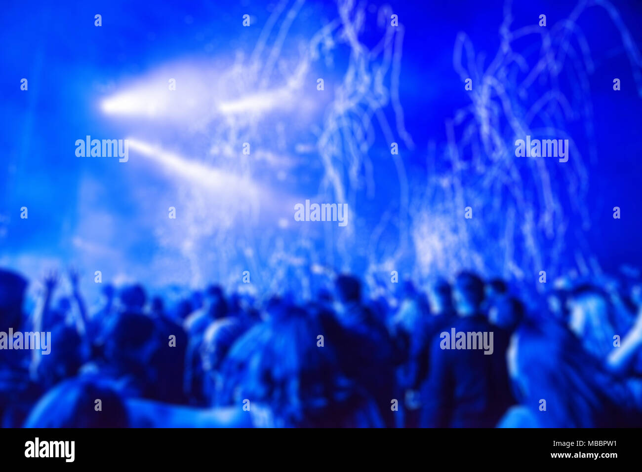 Blurred Background With Crowd Of People Partying And Stage Lights At A Live Concert