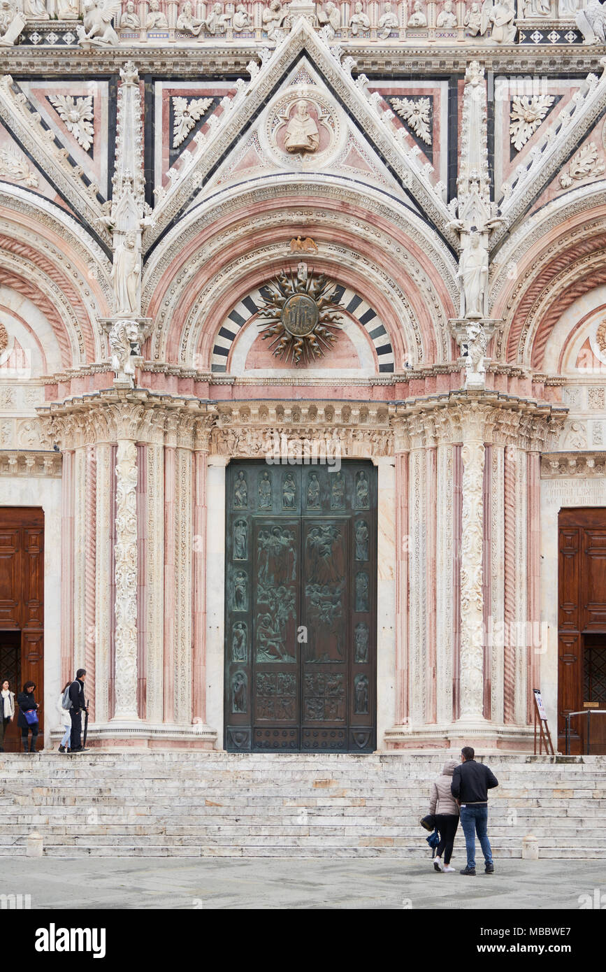 Siena, Italy - Febuary 16, 2016: Front doors of Siena Cathedral, a medieval church built in the Romanesque and Italian Gothic style. It is famous for  - Stock Image