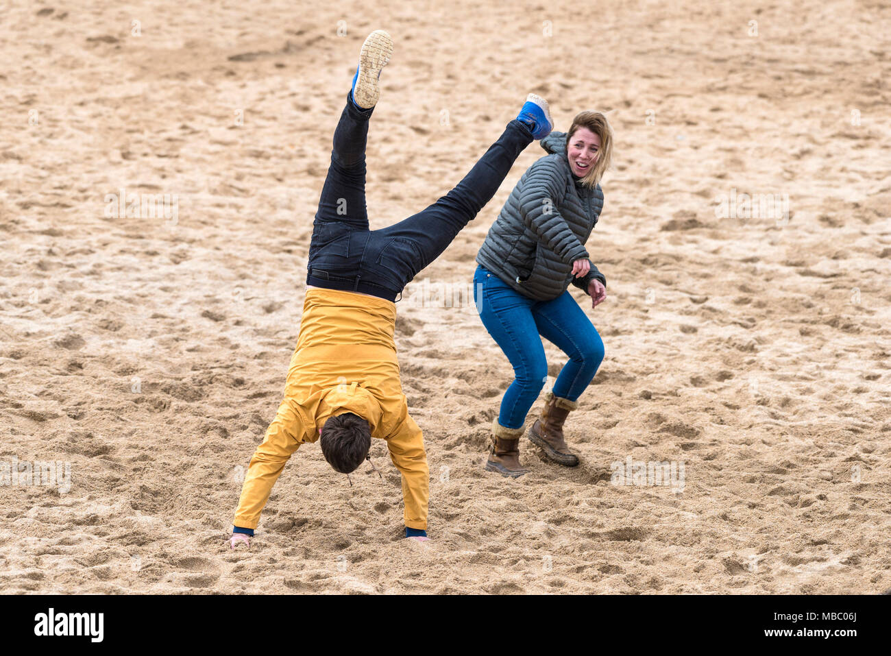 A man attempting to perform a cartwheel on Fistral Beach in Newquay Cornwall. - Stock Image