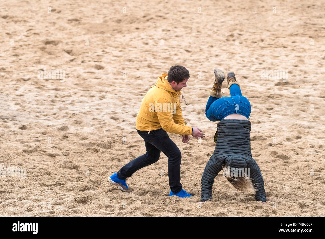 A man attempting to help his wife perform a handstand on a beach. - Stock Image