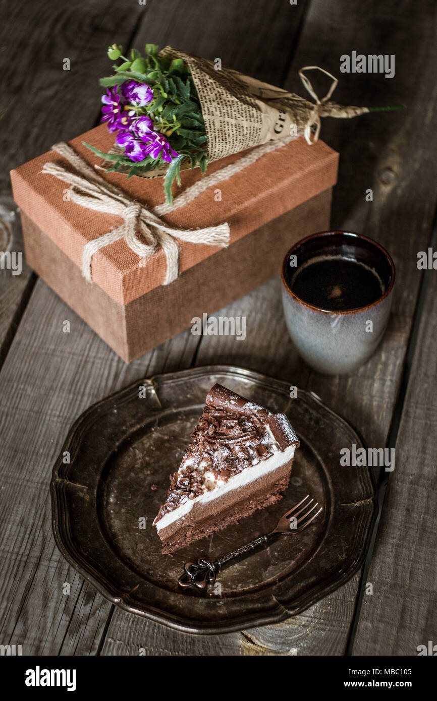 Chocolate birthday cake with flowers cup of coffee and present box chocolate birthday cake with flowers cup of coffee and present box on a wooden table izmirmasajfo