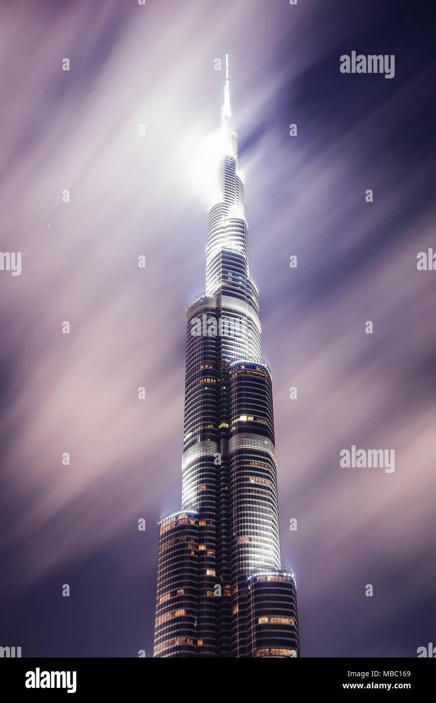 DUBAI, UAE - MAR 23, 2014: Tallest skyscraper of the world called Burj Khalifa during night with motion clouds, Dubai, United Arab Emirates - Stock Image