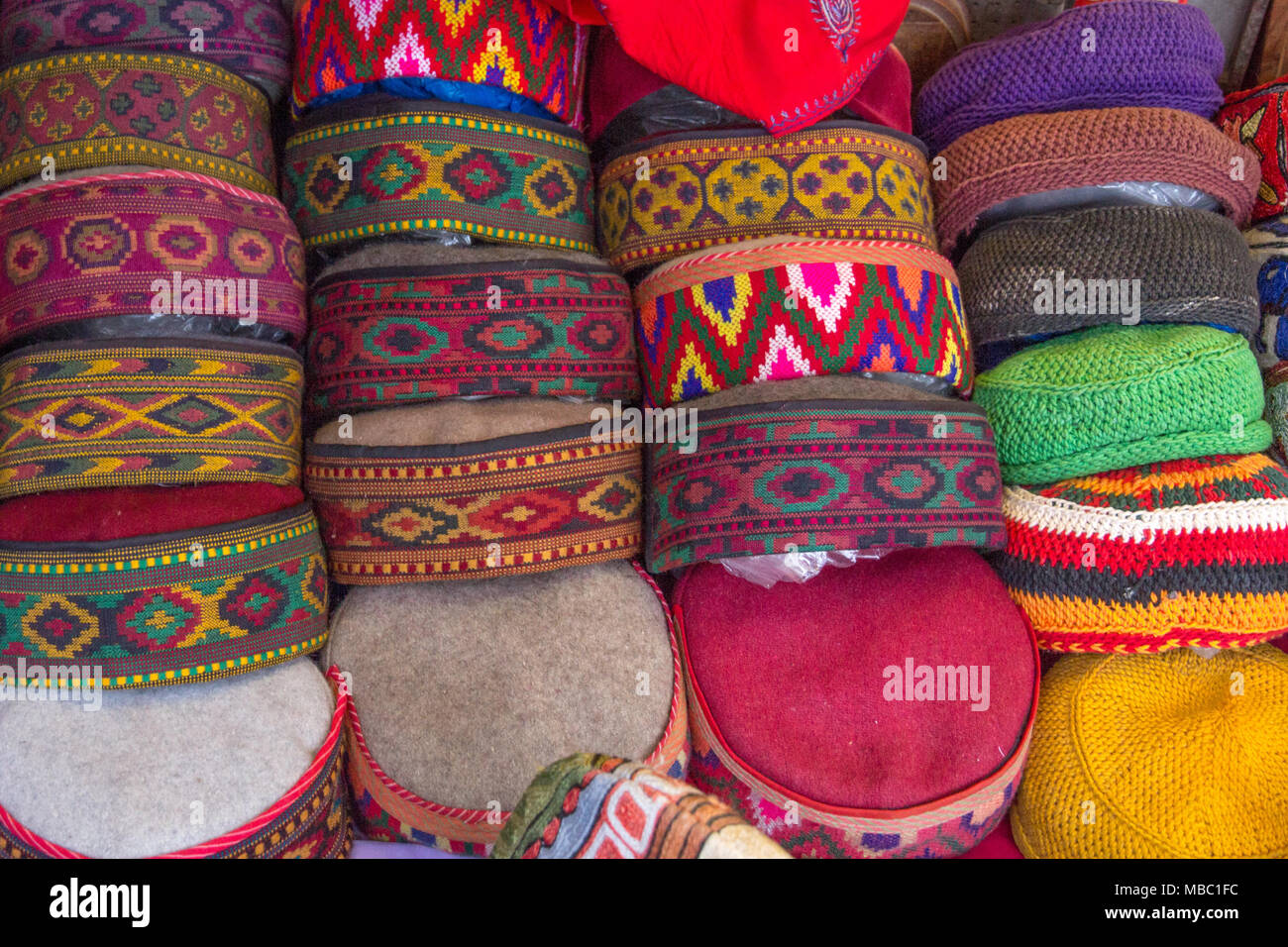 Unique, intricate, woven designs on an array of colorful, flat-topped caps for sale in a Manali market. - Stock Image