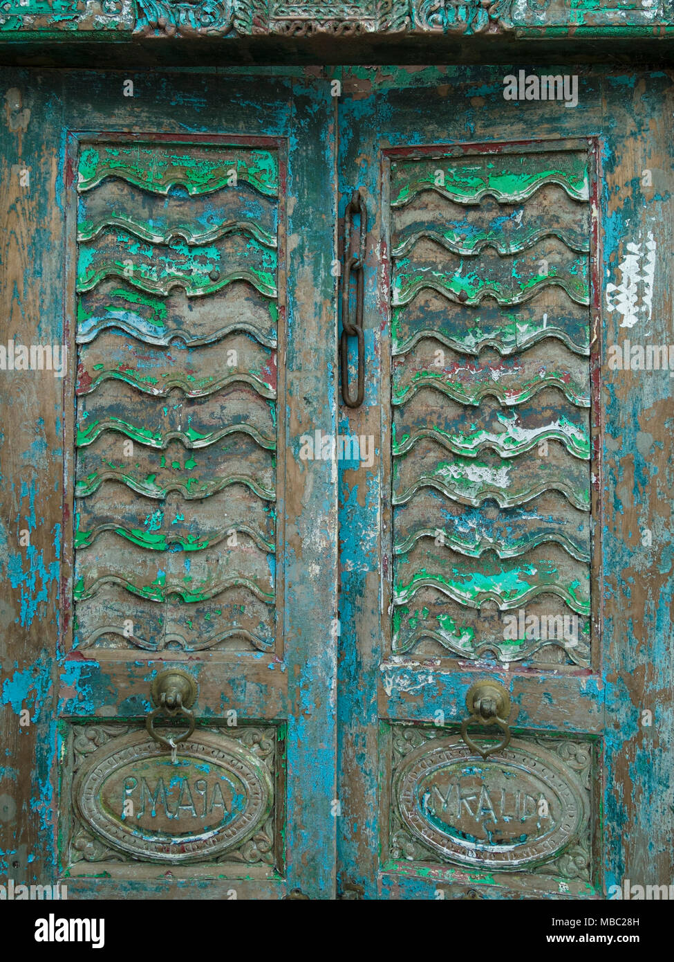 Old distressed ornate antique wooden double doors in Garden Classics reclamation Yard, Ashwell, Rutland, UK - Stock Image