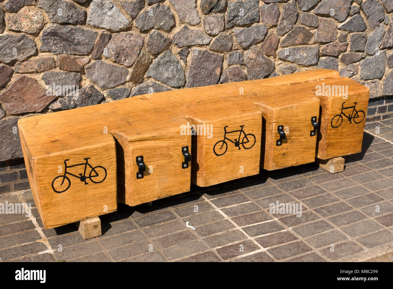 Large wooden log cut with slots to make a cycle rack Stock